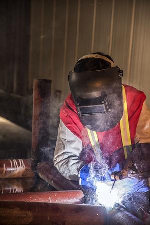 Werknemer die het staaldeel door handboek bij Bouwwerf lassen Stockfoto