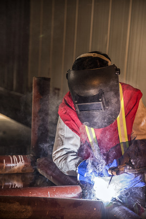 Worker welding the steel part by manual at Construction Site Reklamní fotografie