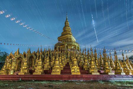 De gouden pagoden met startrail bij Watpa-sawangboon in Saraburi, Thailand. Stockfoto