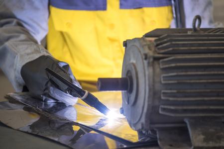 welded: Worker welding the steel part by manual Stock Photo