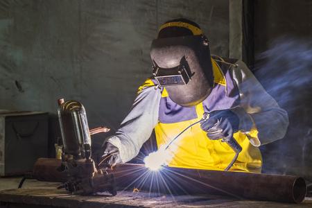 수동으로 강철 부품을 용접하는 작업자 스톡 콘텐츠