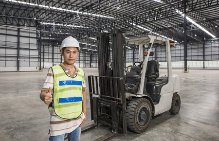 just in time: worker with a forklift in a warehouse in logistic area Stock Photo