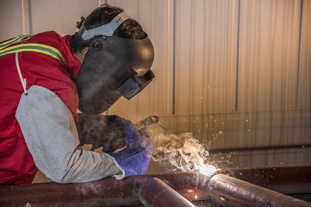 Worker welding the steel part by manual Reklamní fotografie - 50248475