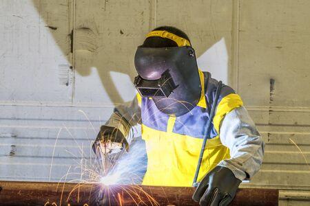 Worker welding the steel part by manual Reklamní fotografie - 50248543