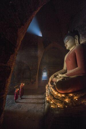 Zuidoost-Aziatische neofiet bidden met kaarslicht in een Buddihist tempel in Bagan, Myanmar Stockfoto