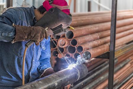 steel: Worker welding the steel part by manual Stock Photo
