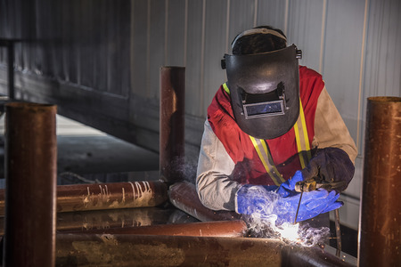 welding mask: Worker welding the steel part by manual at Port Stock Photo