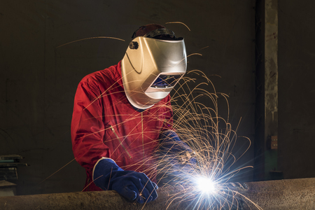 welding mask: worker welding pipeline in a construction area Stock Photo