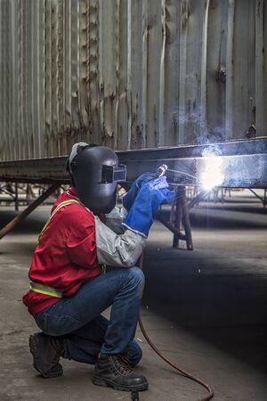 Werknemer het lassen van de stalen deel met de hand in Port Stockfoto