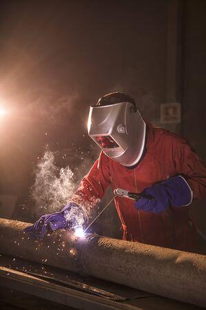 arbeider lasmetaal in de fabriek en vonken