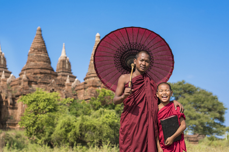 Portrait of novice with umbrella in front of a pagoda temple in Bagan, Myanmar