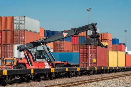 Forklift handling the container box from Freight train to truck in logistics area Stockfoto