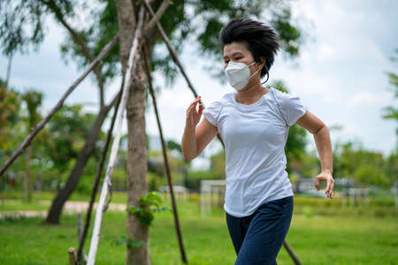 Asian woman wearing face mask while she running in public park after coronavirus outbreak and city lockdown a new normal life. social distancing, new normal, covid-19 or running concepts