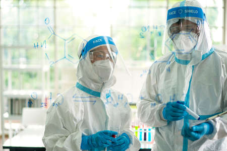 Asian scientist and medical staff in ppe suit analyzing and researching a sample of coronavirus vaccine in virus laboratory. coronavirus, vaccination, virus laboratory or microbiologist concept Stock Photo