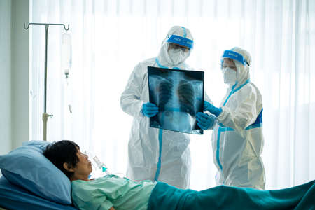 Asian doctor in personal protective equipment or ppe looking at x-ray film of covid-19 or coronavirus infection patient in the hospital. coronavirus, covid-19 outbreak, or medical hospital concept Stock Photo - 153584042
