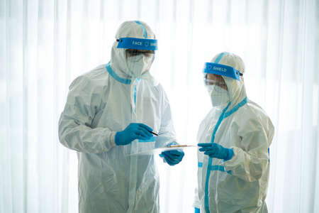 Asian doctor holding checking coronavirus or covid-19 infected patient name list sheet in quarantine area in hospital. Corona virus, Covid 19 virus outbreak, medical mask or virus outbreak concept Stock Photo