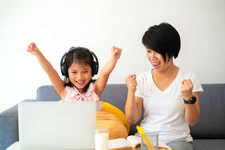 Asian girl and her mother using laptop for online study during homeschooling at home.