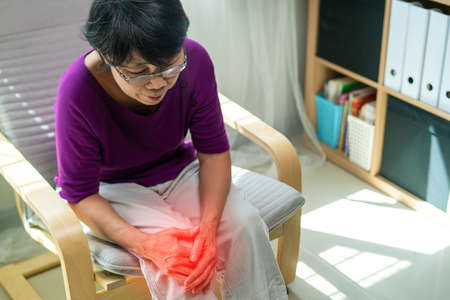 Old woman suffering from pain in her knee a health problem of old age woman. Stockfoto