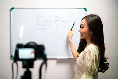 Asian female teacher broadcasting and recording her teaching class for her homeschooling student during coronavirus epidemic.