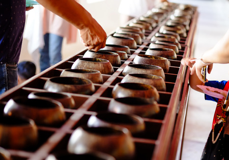 belive: Buddhist Put coin in  monks alms bowl because they belive donation make hapiness and good luck