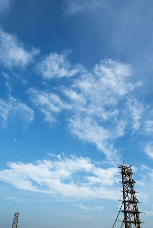 scaffolds: Bridge in construction against blue sky and fluffy clouds in vertical view Stock Photo