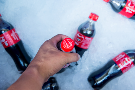 crushed cans: BANGKOK, THAILAND - november 11,2015:  Holding 450 ml. Coca-Cola bottle in ice bucket. Coca Cola in Thailand known as Coke.