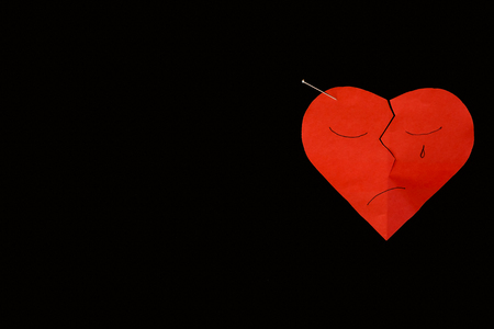 paper pin: Red paper broken heart and crying on black background, with pin. Stock Photo