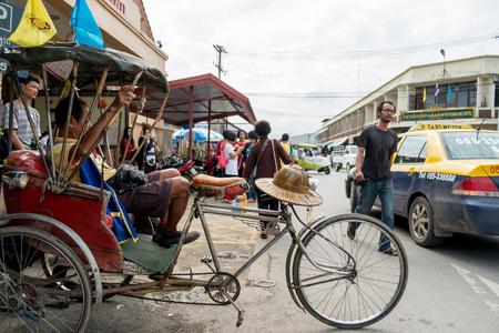 trishaw: Phitsanulok, Tailand- December 6, 2015 : Trishaw driver resting on his vehicle among traffic at frontside of railway station, by the way Phitsanulok railway station establish since january 24, 1907.  at Phitsanulok, Thailand