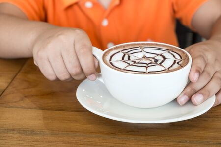 hot cocoa: Kid hand holding creamy hot cocoa cup. Selective focus. Stock Photo