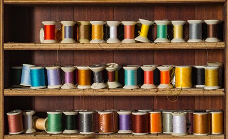 old spools: Old and colorful thread spools on wooden shelf.