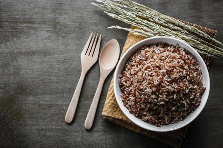 Arroz integral / arroz gruesa con una cuchara de madera y tenedor, semillas de arroz. Vista superior.