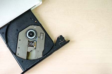 portable rom: Portable CDDVD drive on wooden background. Slim, external Stock Photo