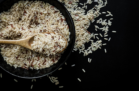 milled: Milled brown rice on wooden spoon and bowl. dark background.