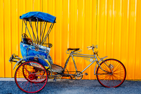 autorick: Old thai Cycle rickshaw Trishaws against yellow wall on background. colorful and useful for travel concept.