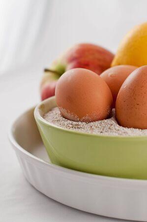 composición con huevos y fruta en un plato para hornear y un cuenco  Foto de archivo