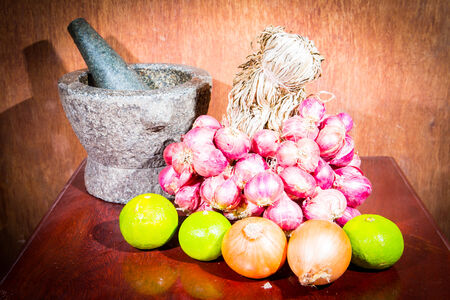 Onions, shallots, lemon, mortar on a wooden background.