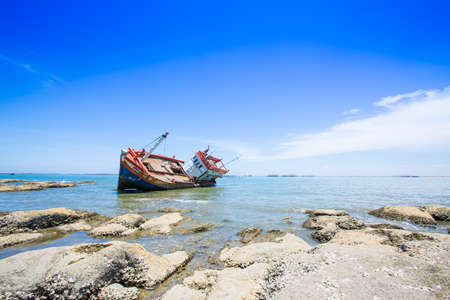 Shipwreck washed up on shore, bright blue sky in background.