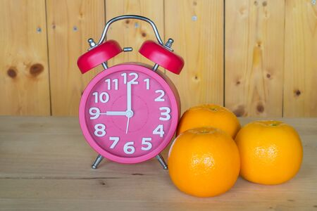 Alarm clock, orange on a wooden background.