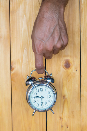8 years old: Alarm clock, clock hands on a wooden background.