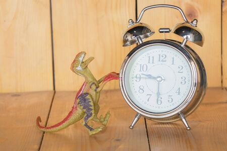 Alarm clock, Dinosaur on a wooden background.