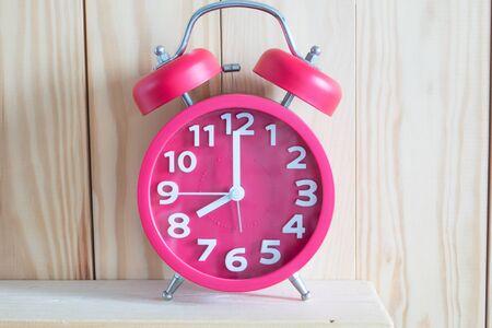 Alarm clock  on wooden background.