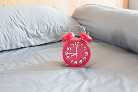 8 years old: Alarm clock, on a bed background.