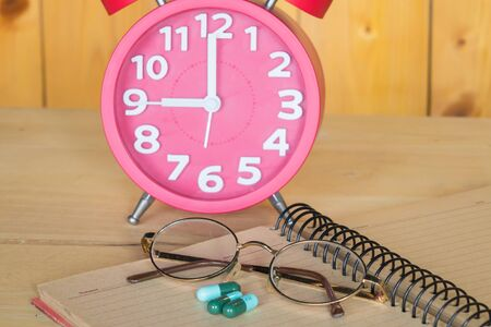 Alarm clock, glasses, medicine books.on a wooden background.