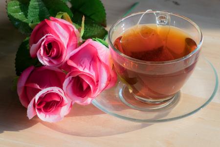 71732528-flores-de-rose-con-el-t%C3%A9-caliente-en-una-tabla-de-madera-.jpg