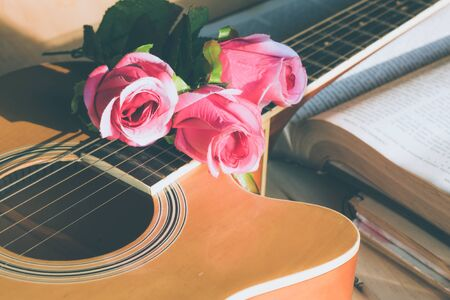 music lyrics: Rose flowers on a book with a guitar on a wood table.