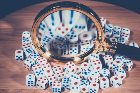 A magnifying glass with many dice.