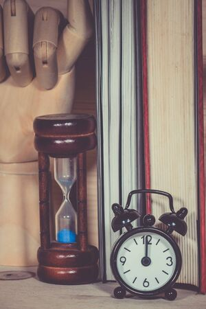 oil lamp: Clock Hourglass Alarm with book on wooden desk