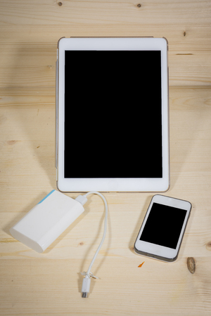 adapters: Power Bank Phone Tablets On a wooden background