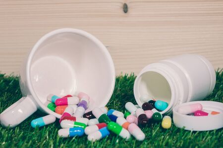 hormonal: Capsules and pills on grass background ,Maintain health from many causes. Stock Photo