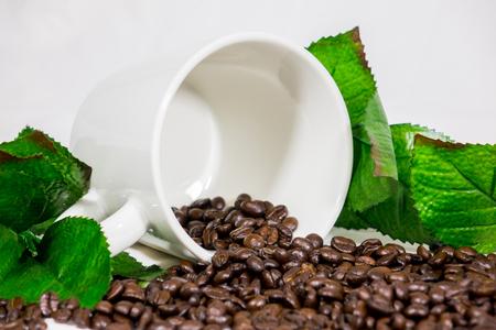 コーヒー豆、白い背景の上のカップ